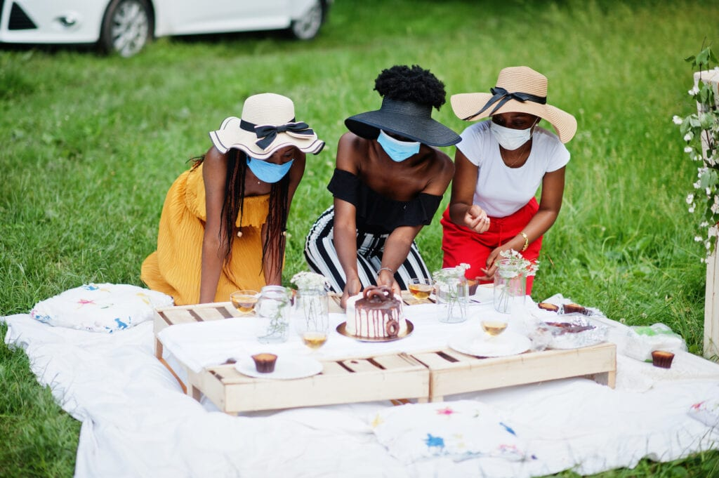 Group of african american girls with facial masks celebrating birthday outdoor party with decor during coronavirus pandemia.