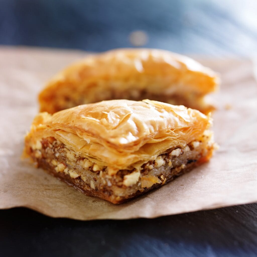 two pieces of baklava on wax paper